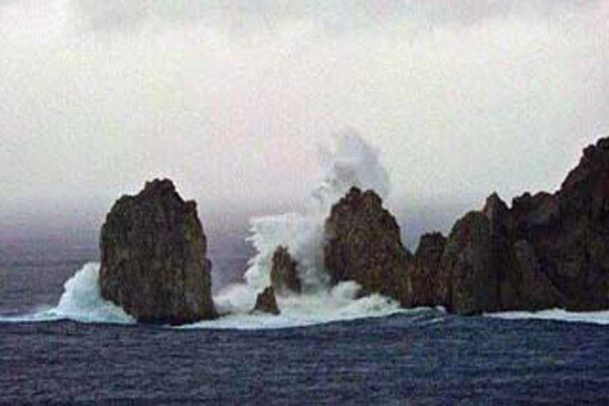 Surf breaks over the obscured top of the famous Land's End Arch